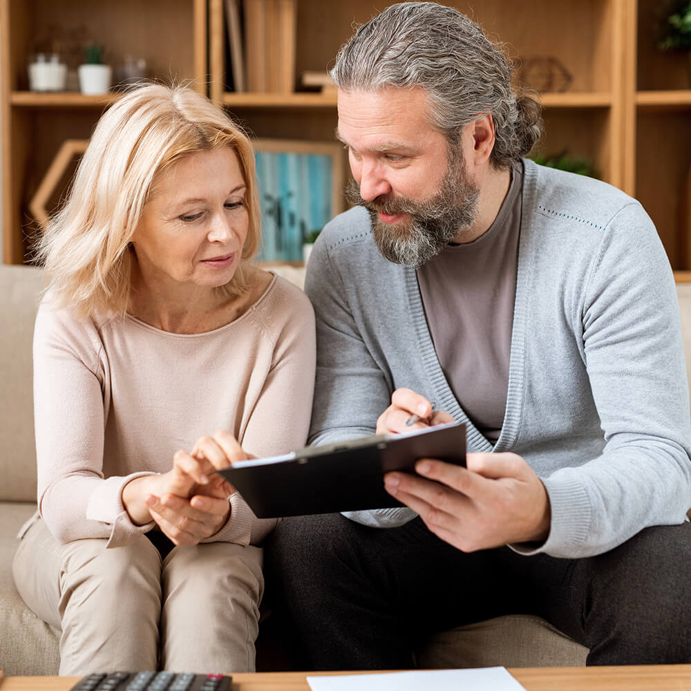 Middle age couple discussing insurance options sitting on sofa
