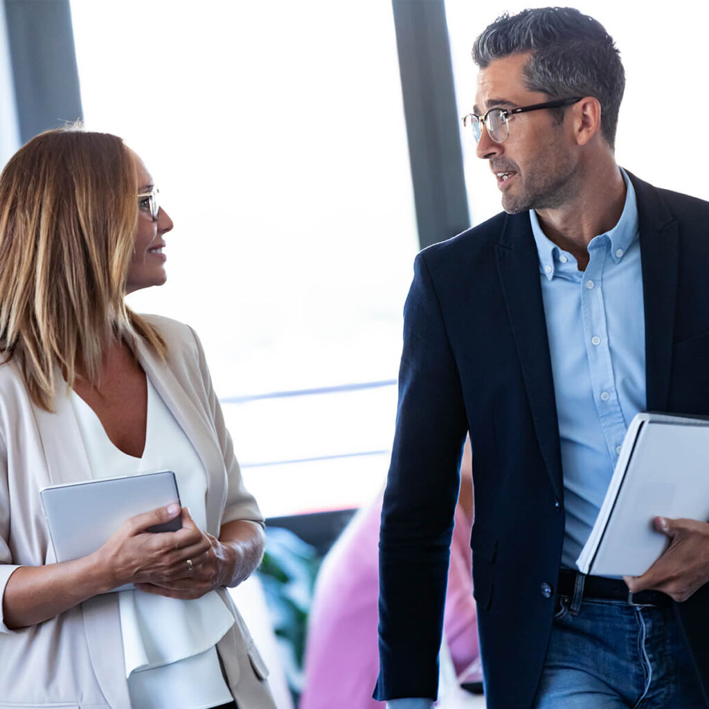 Professional man and woman talking about group benefits and employee benefits insurance