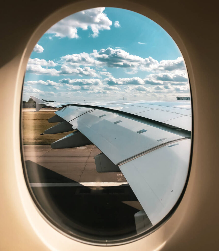 View of an airplanes wing and a blue sky from its inside window